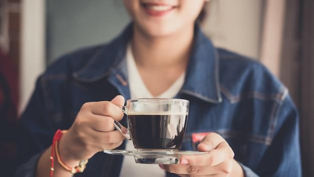 Frau, die eine tasse heißen kaffee hält