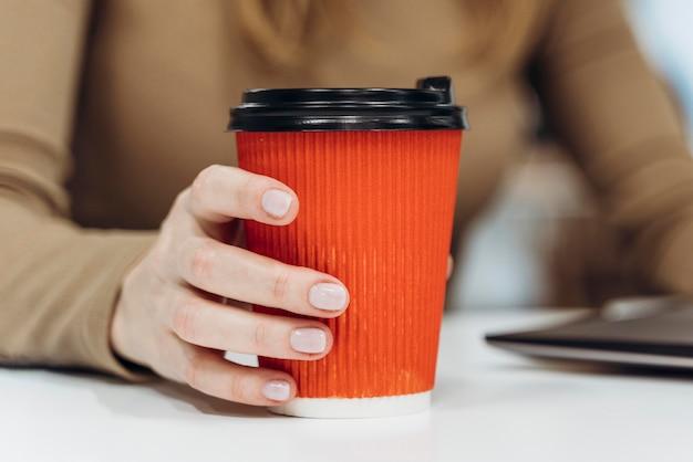 Frau, die eine tasse kaffee bei der arbeit hält