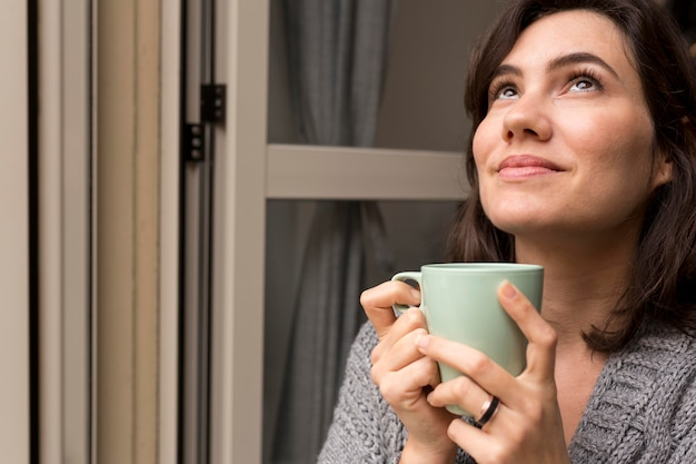 Frau, die eine tasse kaffee beim aufschauen hält