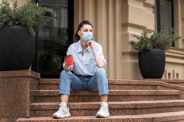 Frau, die eine tasse kaffee hält, während auf treppen mit kopienraum sitzt