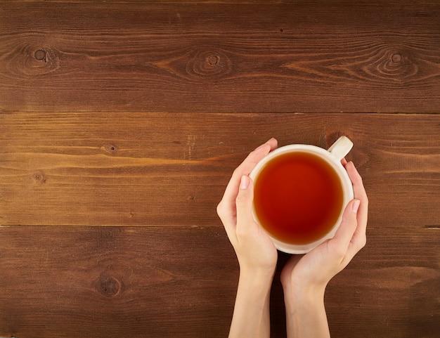Frau, die eine tasse tee auf dunklem holz hält