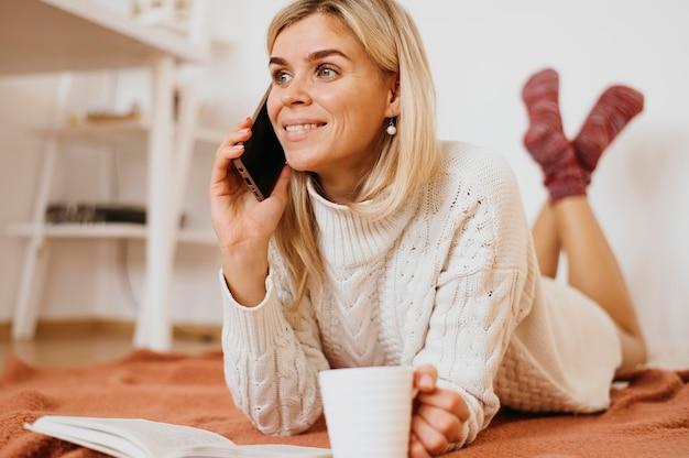 Frau, die eine tasse tee hält und am telefon spricht