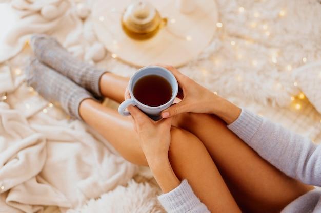 Frau, die eine tasse tee hält, während die winterferien genießt