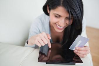 Frau, die eine Tasttablette berührt und eine Kreditkarte in einem Wohnzimmer hält