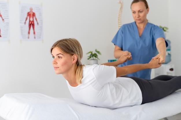 Frau, die eine übung in einer physiotherapiesitzung praktiziert