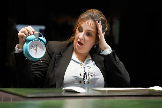 Frau, die eine uhr hält. frau hält einen wecker in der hand am arbeitsplatz.