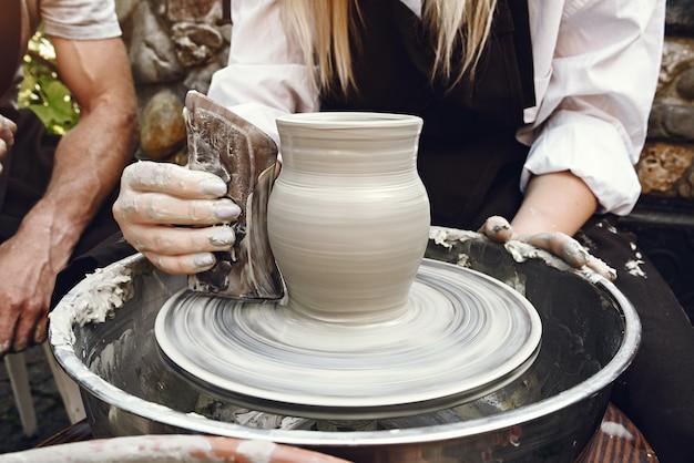 Frau, die eine vase mit ton macht