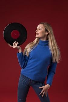 Frau, die eine vinylscheibe hält