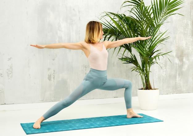 Frau, die eine virabhadrasana ii-vorwärts-longe-yoga-pose macht, um ihre kniesehne zu dehnen und zu stärken