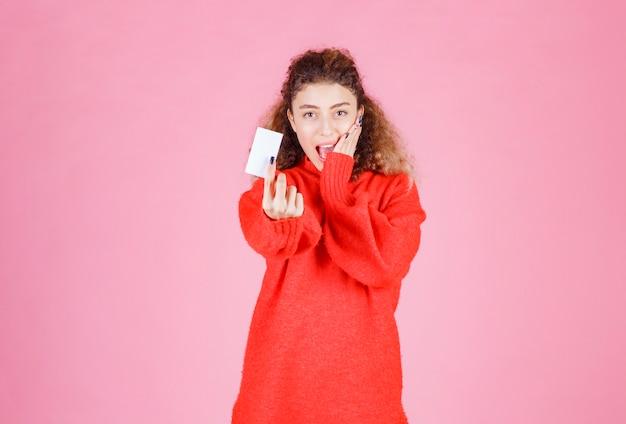 Frau, die eine visitenkarte hält, sieht sehr glücklich und überrascht aus.