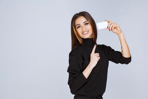 Frau, die eine visitenkarte hält und sich vorstellt.
