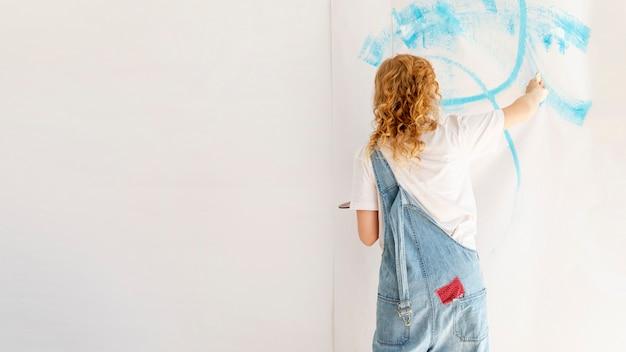 Frau, die eine wand mit kopieraum malt