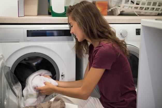 Frau, die eine waschmaschine anmacht