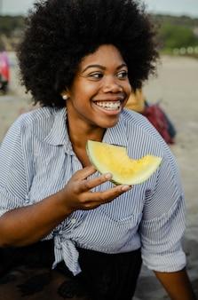 Frau, die eine wassermelone an einem strandpicknick isst