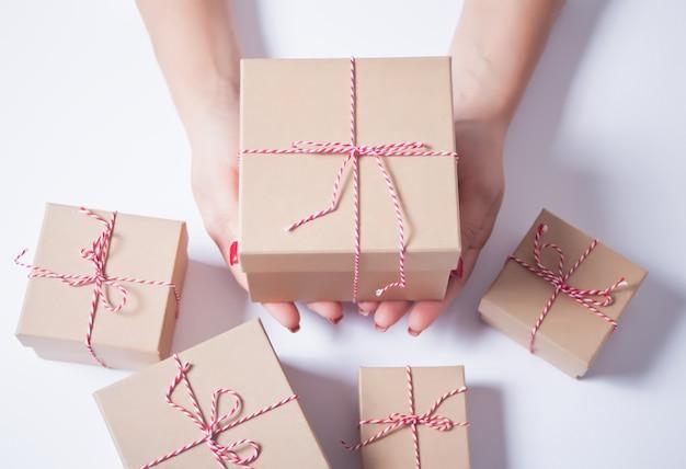 Frau, die eine weihnachtsgeschenkbox in hände hält
