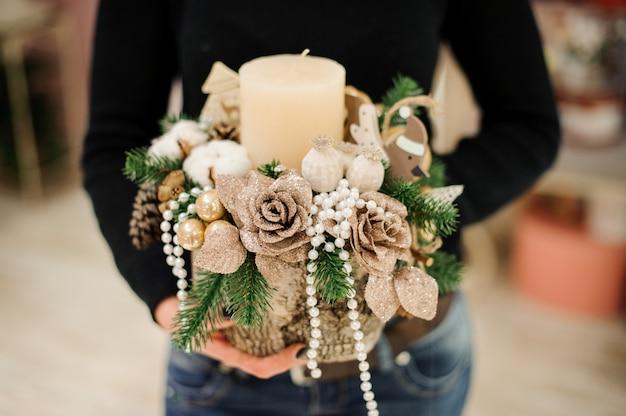 Frau, die eine weihnachtskomposition aus kerze, beige rosen, kugeln und perlen und tannenbaum hält