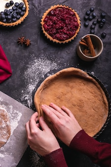 Frau, die eine weihnachtspastete mit kirsche vorbereitet