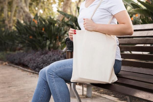 Frau, die eine weiße einkaufstasche hält und auf bank sitzt
