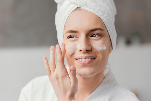 Frau, die eine weiße gesichtscreme verwendet