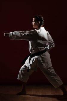 Frau, die eine weiße karateuniform locht und trägt
