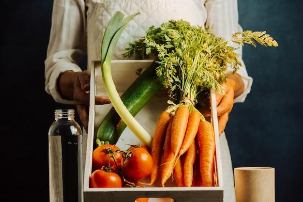 Frau, die eine weiße schachtel des gemüses über einem tisch mit wasser nahe ihrem gesunden lebensmittelkonzept mit kopienraum hält