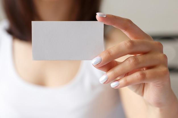 Frau, die eine weiße visitenkarte in seiner hand, nah oben hält