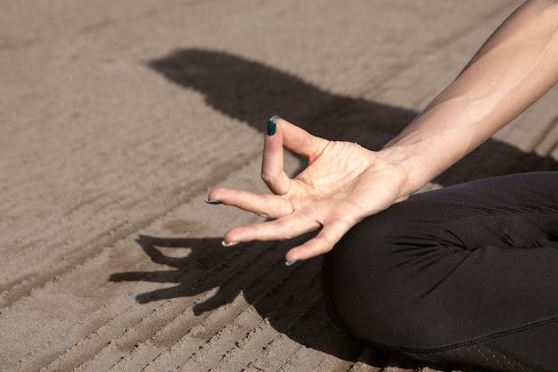 Frau, die eine yoga-pose am strand hält