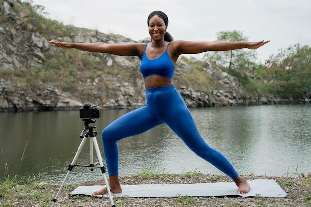 Frau, die eine yoga-pose draußen lehrt