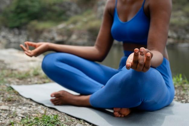 Frau, die eine yoga-pose im freien lehrt