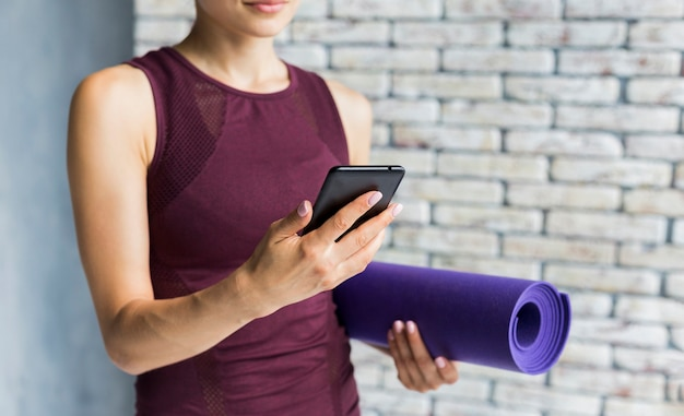 Frau, die eine yogamatte beim betrachten ihres telefons trägt