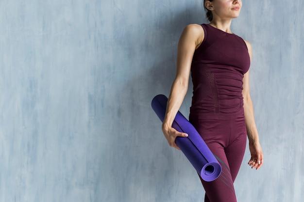 Frau, die eine yogamatte hält
