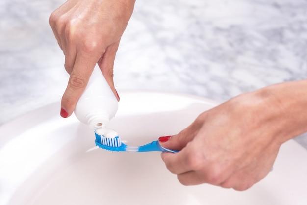 Frau, die eine zahnbürste hält zahnpasta auf sie hält.