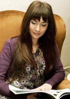 Frau, die eine zeitschrift zur teezeit liest