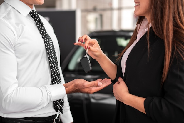 Frau, die einem mann autoschlüssel übergibt