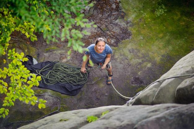 Frau, die einen anderen bergsteiger mit seil sichert
