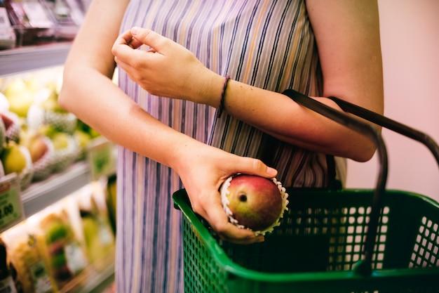 Frau, die einen apfel am supermarkt vorwählt