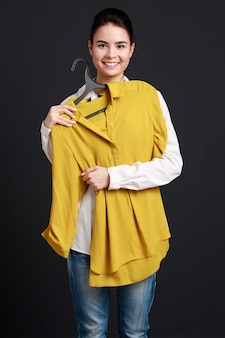 Frau, die einen aufhänger mit einem hemd hält, es an passt und lächelt