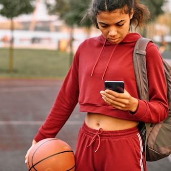 Frau, die einen basketball draußen hält und ihr telefon überprüft