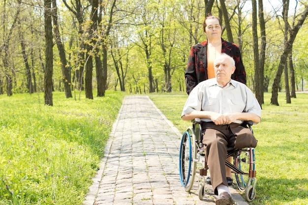 Frau, die einen behinderten mann im rollstuhl geht