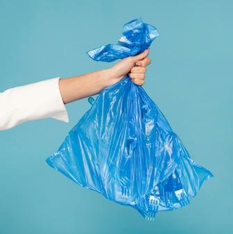 Frau, die einen blauen plastikmüllsack hält