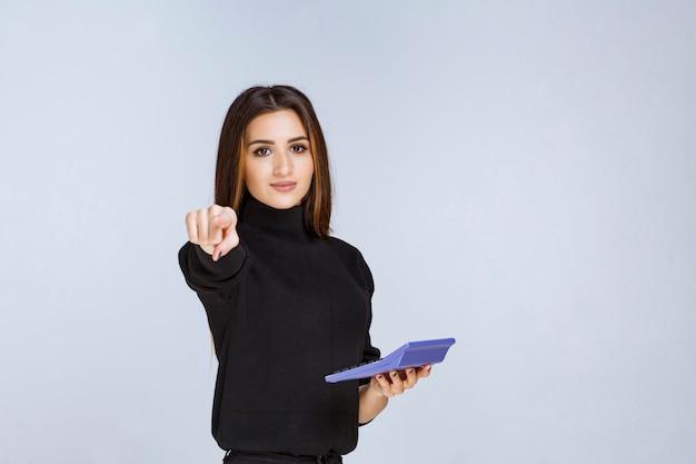 Frau, die einen blauen taschenrechner hält und auf ihren kollegen vor sich zeigt.