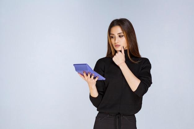 Frau, die einen blauen taschenrechner hält und daran arbeitet.