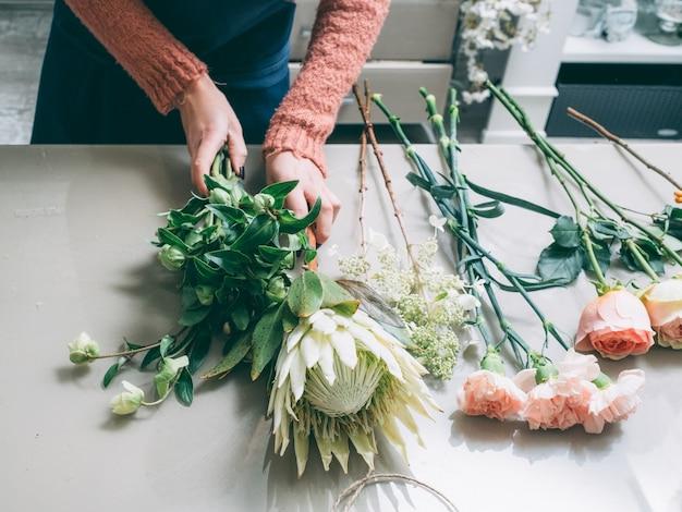 Frau, die einen blumenstrauß aus rosendahlie, goldenem gänseblümchen und jasmin macht. lieferung von blumenarrangements.