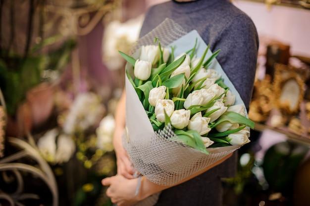 Frau, die einen blumenstrauß der weißen tulpen eingewickelt in einem papier anhält