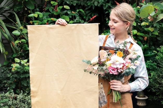 Frau, die einen blumenstrauß mit einem plakat hält