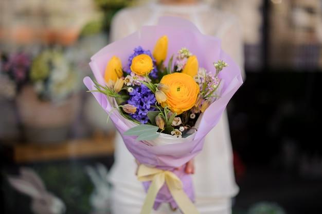 Frau, die einen blumenstrauß von gelben pfingstrosenrosen und von violetter blauer hyazinthe hält