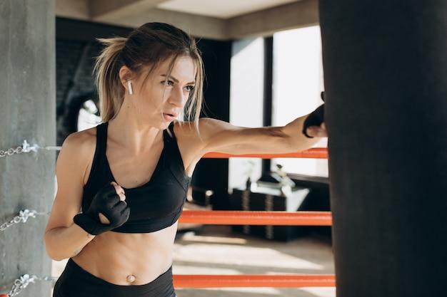 Frau, die einen boxsack mit boxhandschuhen an der turnhalle locht. konzept über sport, fitness, kampfsport und menschen