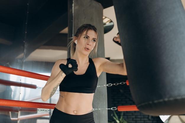 Frau, die einen boxsack mit boxhandschuhen an der turnhalle locht