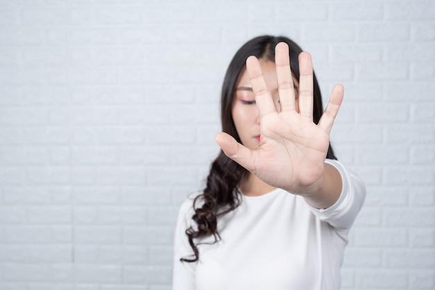 Frau, die einen braunen briefkasten hält machte gesten mit gebärdensprache.