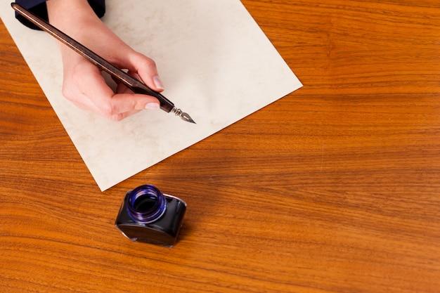 Frau, die einen brief mit feder schreibt